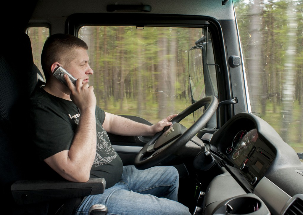 A truck driver on the road talking on his cell phone